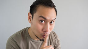Man tells secret. Asian man is telling a secret. Do not tell anyone stock photo