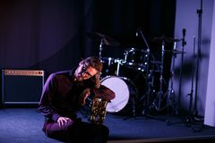 Man tenderly holding a saxophone while seating on a stage. Pink lightning Stock Image
