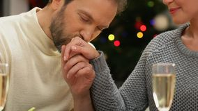 Man tenderly kissing woman hand, romantic date on Christmas night, closeup