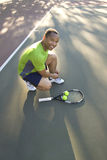 Man on Tennis Court Tying His Shoe Stock Photo