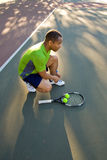 Man on Tennis Court Tying Shoe Royalty Free Stock Image