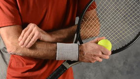 Man with tennis elbow. Man massaging arm with tennis elbow