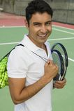 Man with tennis racket and balls on tennis court portrait Stock Photo