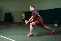 Man with tennis racket playing on indoor court Royalty Free Stock Images
