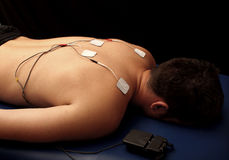 Man with TENS on his back. Muscle electrical stimulation therapy with TENS Royalty Free Stock Photo