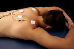 Man with TENS on his back. Muscle electrical stimulation therapy with TENS Royalty Free Stock Photos