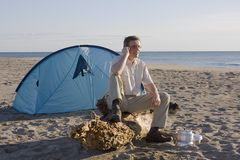 Man with tent on beach. Man sitting in front of his tent on a beach while making a phone call Stock Photography