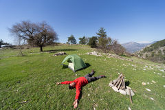 Man with tent camping. Man camping with a tent in the mountains in the summer on a sunny day Royalty Free Stock Image