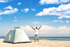Man with tent enjoying camping on beach Stock Images