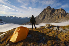Man with tent observes the Alps Royalty Free Stock Photo