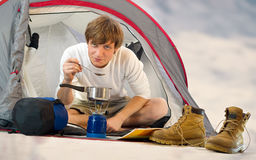 Man in a tent outdoor and cooking Stock Images