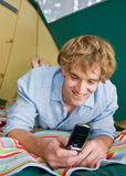 Man in tent text messaging on cell phone Royalty Free Stock Photography