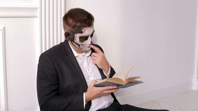 A man with a terrible make-up in the form of a skull is holding a book.Halloween. A man with a terrible make-up in the form of a skull is holding a book in his stock video