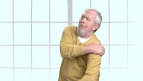Man with terrible shoulder pain, portrait. Elderly man suffering from severe shoulder pain indoor. Causes of shoulder pain stock video footage