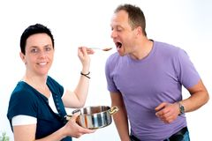 Man test the good food of his wife Stock Photos