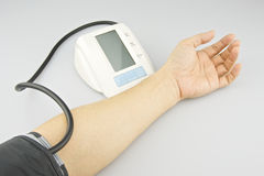 Man is testing blood pressure on left arm Stock Image