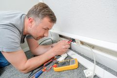 Man testing current behind skirting board royalty free stock images