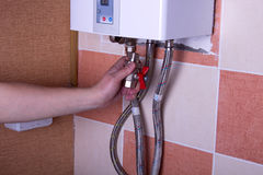 Man tests the reliability of fastening of pipes in water heater Stock Photography