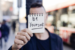 Man and text be yourself in a note. Closeup of a young caucasian man in the street showing a notepad with the text be yourself written in it royalty free stock photography