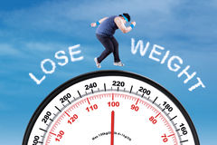 Man with text lose weight and scale. Overweight man running above a scale with text lose weight, shot under blue sky Stock Photography