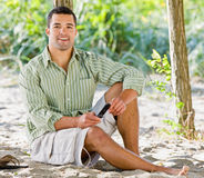 Man text messaging on cell phone at beach Stock Image