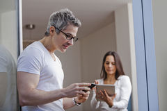 Man text messaging with his wife using a digital tablet Stock Image