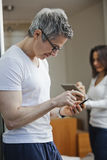 Man text messaging with his wife using a digital tablet Stock Photography