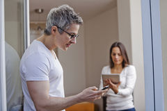 Man text messaging with his wife using a digital tablet Royalty Free Stock Images