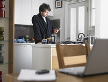 Man Text Messaging In Kitchen Stock Photography