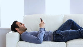 Man text messaging laid on the couch stock video footage