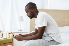 Man text messaging on mobile phone in bedroom Stock Images
