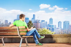 Man text from phone with Seattle downtown on back Stock Photo