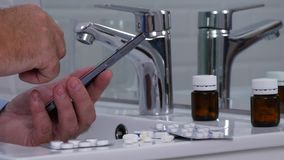Man Text Using Cellphone in Bathroom with Pills and Drugs on the Sink.  stock video footage