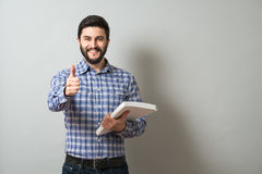 Man with textbook. Delightful bearded man holds textbook and show thumb up gesture. Education or business concept Royalty Free Stock Photo