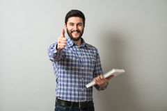 Man with textbook. Delightful bearded man holds textbook and show thumb up gesture. Education or business concept Stock Photo