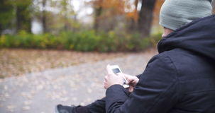 Man Texting on Bench in Autumn Park. stock video
