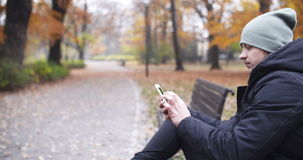 Man Texting on Bench in Autumn Park. stock video footage