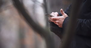 Man Texting on Bench in Autumn Park. stock footage