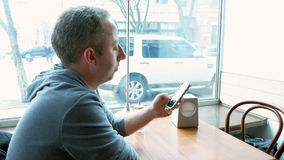 Man texting and browsing with mobile app in a cafe stock footage
