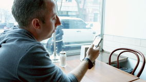 Man texting and browsing with mobile app in a cafe stock video