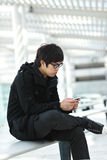 Man texting on cell phone. Asian young man texting on cell phone Royalty Free Stock Photo
