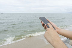 A man texting cellphone on the beach. A man using left index finger for texting cellphone on the beach Royalty Free Stock Photography