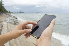 A man texting cellphone on the beach Stock Photo