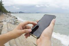 A man texting cellphone on the beach. A man using left index finger for texting cellphone on the beach Stock Photo