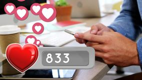 Man texting on a desk. Close up of a man holding his phone on a desk beside a coffee while heart icons are floating in the foreground stock video footage