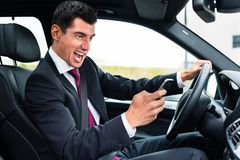 Man texting while driving angrily his car Stock Photos
