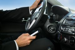 Man texting while driving his car. Close-up Of A Man Holding Cellphone While Driving Car Royalty Free Stock Photos