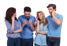 Man texting while friends are talking on phone. Group of casual people talking on the phone and one is reading or writing a text sms message on white background Stock Photo