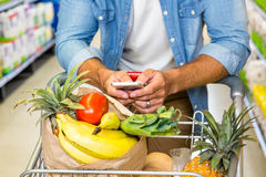 Man texting and grocery shopping Royalty Free Stock Photo