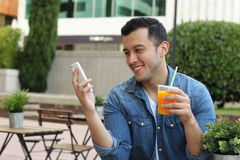 Man texting while having a fresh orange juice at an outdoors cafe.  Royalty Free Stock Image